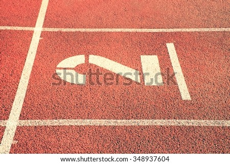Number two. Big white track number on red rubber racetrack. Gentle textured racetracks in small outdoor stadium. - stock photo