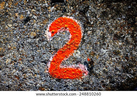 number two on the stone wall painted with paint - stock photo