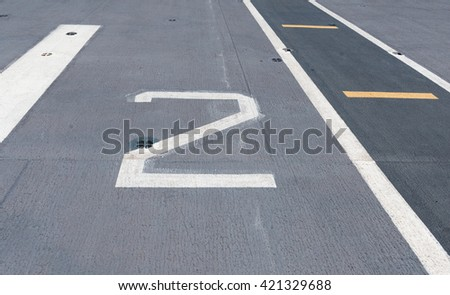 number two on white and yellow runway. - stock photo