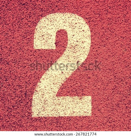 Number two. White track number on red rubber racetrack, texture of running racetracks in small stadium - stock photo