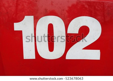 number 102   white on red painted metal