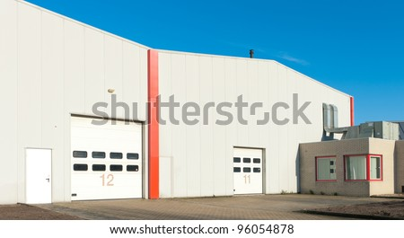 numbered industrial roller doors in a large warehouse - stock photo