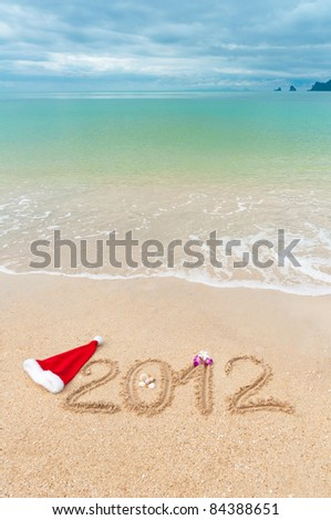 Numbers 2012 and santa hat on tropical beach sand - vertical holiday background - stock photo