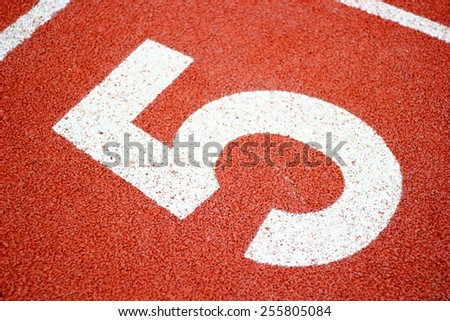 Numbers five on  running track. - stock photo