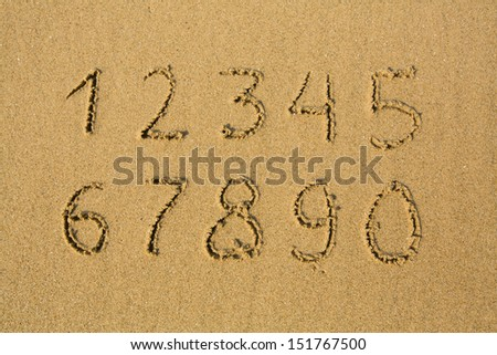 Numbers from one to ten, written on a sandy beach.  - stock photo