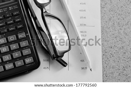 numbers in columns statement with pencil glasses and calculator - stock photo