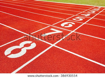 Numbers on athletics running track background and grass. Futbol greensward. - stock photo