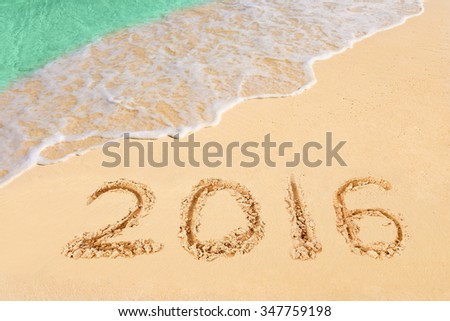 Numbers 2016 on beach - concept holiday background - stock photo