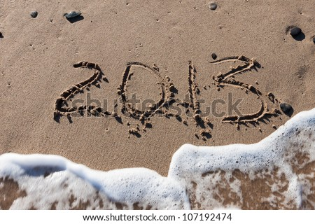 Numbers 2013 on sea beach sand with tide wave water - stock photo