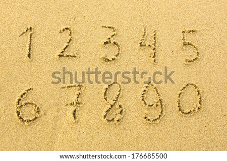 Numbers one to ten written on a sandy beach. - stock photo
