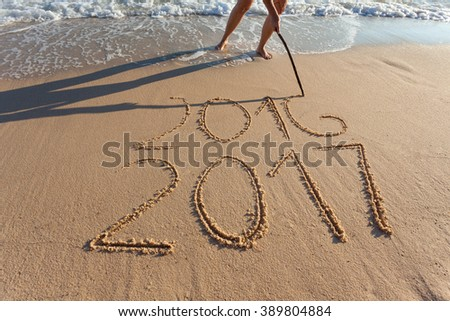 Numbes 2017 and 2016 handwritten on seashore sand. Concept of upcoming new year and passing of time. - stock photo