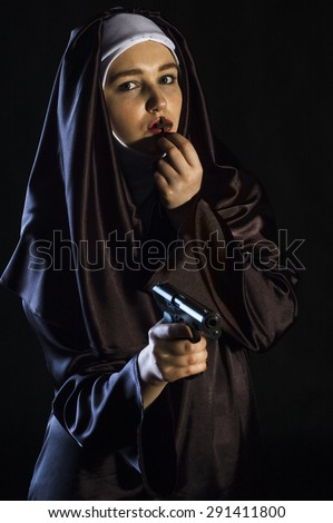 Nun holding gun in one hand and cross in another. isolated on black background.