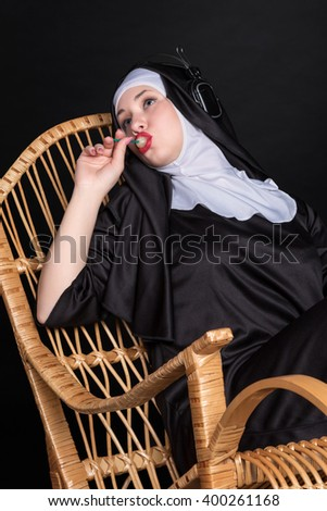 Nun sitting in a rocking chair sucking candy and listening to music on headphones - stock photo
