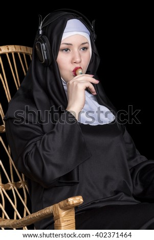 Nun sitting in a rocking chair sucking candy and listening to music on headphones close-up - stock photo