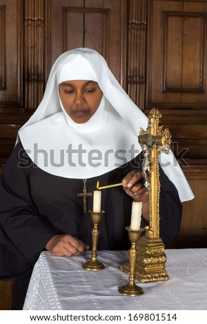 Nun standing at the altar and lighting a candle - stock photo