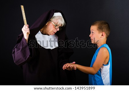 Nun threatening a young boy with a ruler.