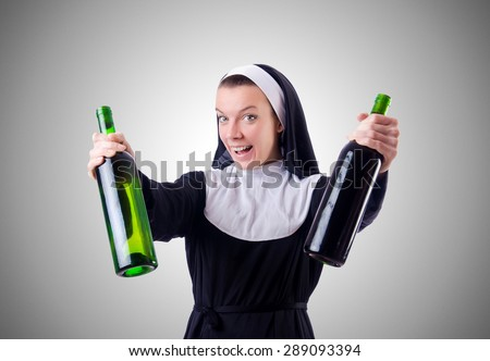 Nun with bottle of red wine - stock photo
