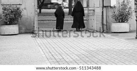 Nuns with habit walking on urban street, religion