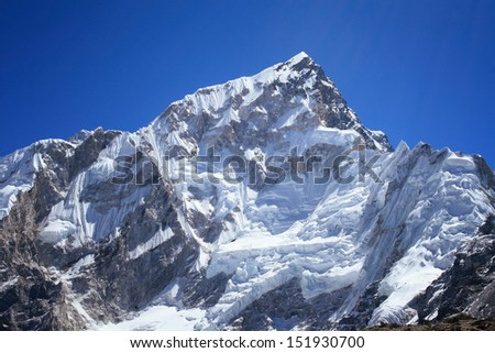 Nuptse mountain against blue sky. Nuptse (7891m) is a mountain in the Khumbu region of the Mahalangur Himal, in the Nepalese Himalayas. It lies two kilometres away of Mount Everest - stock photo