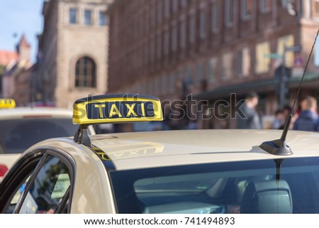 Nurberg, Germany - SEPTEMBER 22, 2016: A close up of taxi brand bright yellow plate in the middle of busy street filled with people in Nuremberg