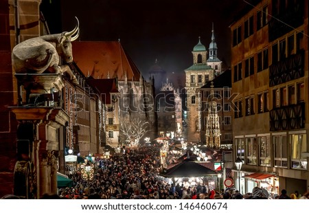 "NUREMBERG, GERMANY - CIRCA DEC 2012 - Big crowds visit the Christmas Market at night circa December 2012 in Nuremberg. Annual ""Christkindlesmarkt"" is one of the biggest Christmas Markets in the world. - stock photo"
