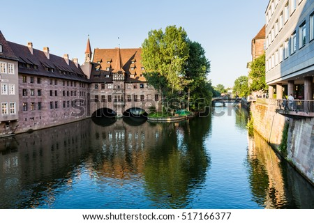 NURENBERG, GERMANY - JUNE 22, 2016: View from a historical arch bridge called Museumsbrucke to the Heilig Geist Hospital in the old town part of Nurnberg on June 22, 2016.