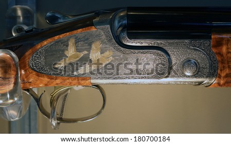 NURNBERG, GERMANY - MARCH 9: Handmade engravings on Caesar Guerini hunting shotguns on display at IWA 2014 & Outdoor Classics exhibition on March 9, 2014 in Nurnberg, Germany - stock photo