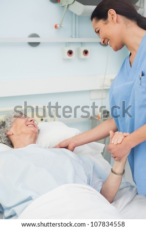 Nurse and a patient smiling in hospital ward