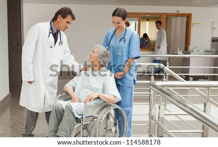 Nurse and doctor talking with old woman sitting in wheelchair in hospital corridor - stock photo