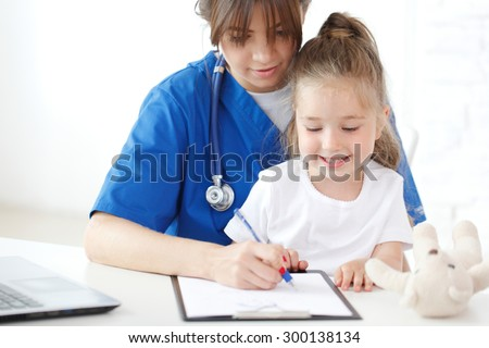 nurse and kid writing medical record - stock photo