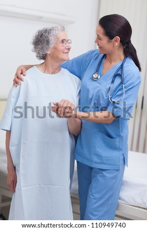 Nurse assisting an elderly patient in hospital ward