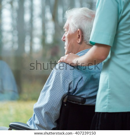 Nurse assisting disabled senior man using wheelchair - stock photo
