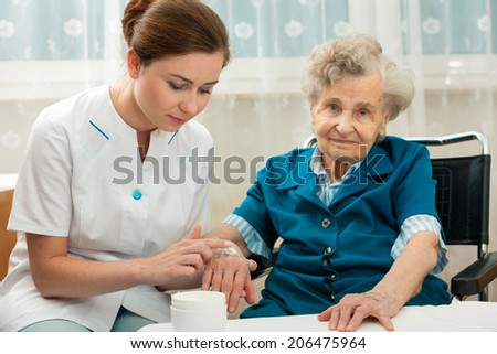 Nurse assists an elderly woman with skin care and hygiene measures at home - stock photo
