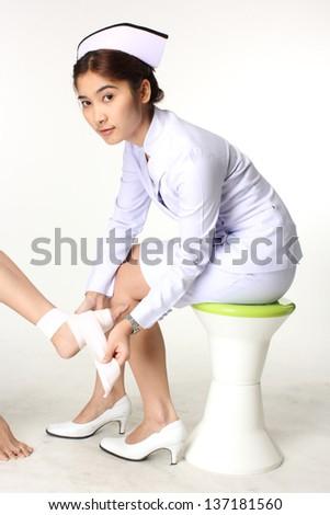 Nurse bandaging patient / Isolate background. - stock photo