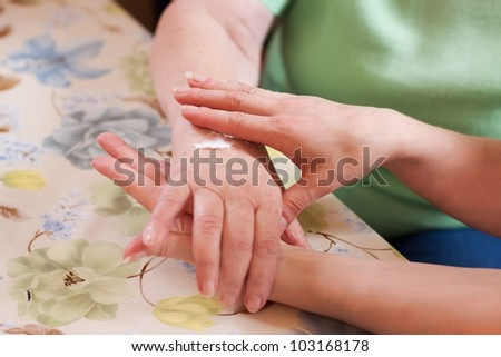 Nurse cares for a senior citizen's hands - stock photo