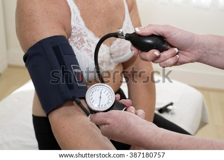 Nurse checking elderly woman's blood pressure using a blood pressure monitor