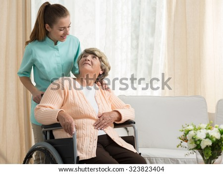 Nurse discussing with elder patient in care home - stock photo