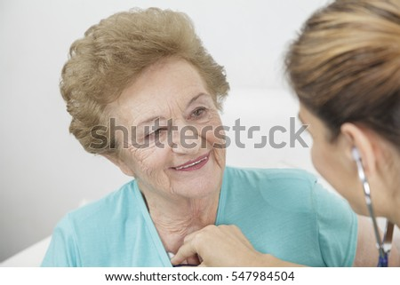 Nurse giving a senior citizen woman a medical checkup