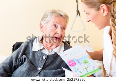 Nurse giving birthday card to senior woman in nursing home sitting in wheelchair - stock photo