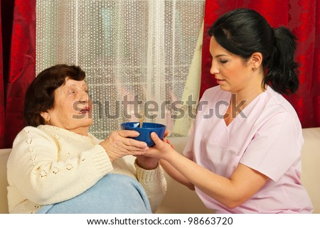Nurse giving bowl with soup to senior woman  home