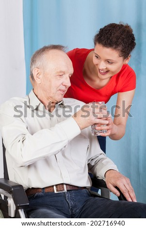 Nurse giving disabled man a glass of water - stock photo