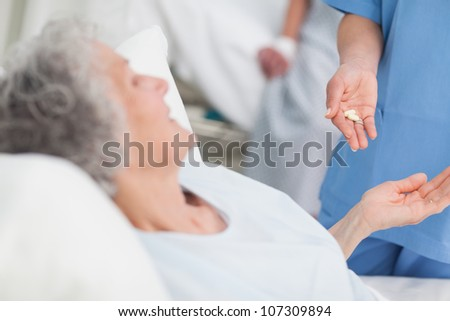 Nurse giving drugs to an elderly patient in hospital ward - stock photo