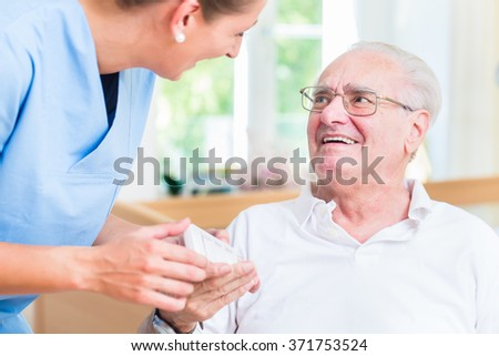 Nurse giving senior man prescription drugs - stock photo
