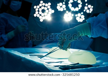Nurse hand taking surgical instrument for group of surgeons at background operating patient .  breast augmentation. - stock photo