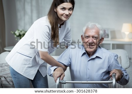 Nurse helping disabled senior man with standing - stock photo