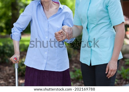 Nurse helping disabled woman with walking in a garden - stock photo