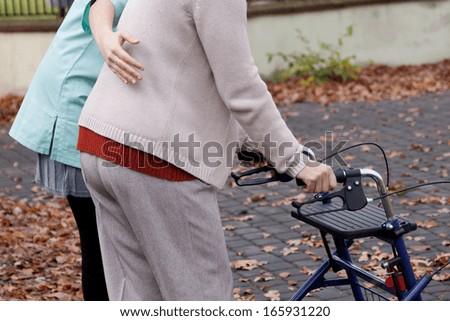 Nurse helping elder person to walk with walker - stock photo