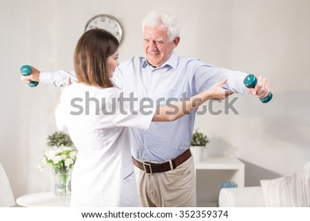 Nurse helping patient to exercise with dumbbels - stock photo