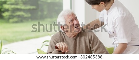 Nurse helping senior man in rest home - stock photo