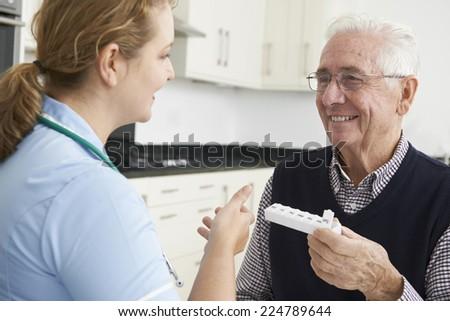 Nurse Helping Senior Man With Medication - stock photo